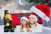 picture of north-pole  - Festive mother and daughter decorating christmas tree against cute christmas village at north pole - JPG