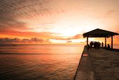picture of waikiki  - Golden hour sunset at a cement rock pier at Waikiki Beach - JPG