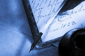 image of inkpot  - Old book with feather and inkpot in closeup