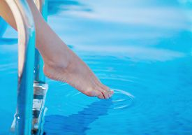 stock photo of wet feet  - Beautiful female foot touches the thumb blue water in the pool at a tropical resort - JPG