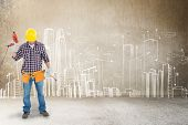 image of hammer drill  - Male repairman holding drill machine and hammer against hand drawn city plan - JPG