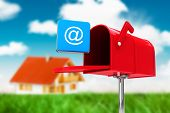 stock photo of postbox  - Red email postbox against house in the distance - JPG