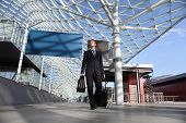 stock photo of board-walk  - Business man travel work look the sign board walking with luggage trolley - JPG