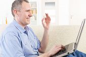 stock photo of deaf  - Smiling Deaf man talking using sign language on the laptop - JPG