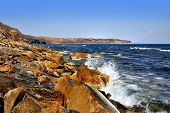 pic of windy  - big orange rocks on the shore in spring in windy day - JPG