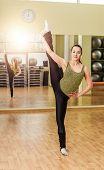 stock photo of do splits  - Young slim woman doing standing split in fitness class - JPG