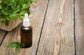 foto of mints  - Essential mint oil with fresh mint on a old wooden background - JPG