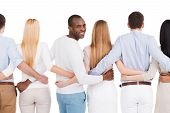 image of bonding  - Rear view of group of diverse people bonding to each other and standing against white background while one African man looking over shoulder and smiling - JPG