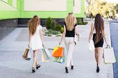 picture of girl walking away  - Girls holding shopping bags and walk around the shops - JPG