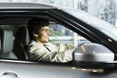image of showrooms  - Handsome young man sitting in car in showroom  - JPG