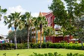 stock photo of curacao  - Colorful resort in Curacao with palm trees in landscaped lawn - JPG