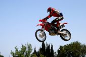 foto of moto-x  - orange and red moto x or moto cross bike jumping over hump on dirt track in sunny marbella with mountain backdrop - JPG