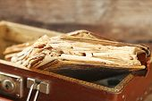 stock photo of old suitcase  - Old wooden suitcase with old books on wooden background - JPG