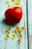 picture of cod  - Red heart and cod liver oil on blue wooden background - JPG
