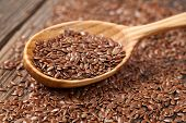 stock photo of flax plant  - Heap of flax seeds super food nutrition in wooden spoon - JPG