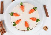 stock photo of carrot  - Homemade carrot sponge cake with little carrots and  cream on white background - JPG