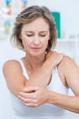 image of elbows  - Woman having elbow pain in medical office - JPG