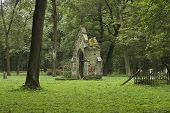 stock photo of burial-vault  - Ruined burial vault on green grass at old cemetery on cloudy day - JPG