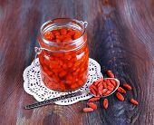 stock photo of doilies  - Goji berries in glass bottle on lace doily with silver spoon on rustic wooden table background - JPG
