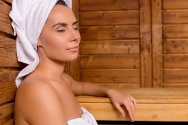 pic of sauna woman  - Attractive young woman wrapped in towel relaxing in sauna and keeping eyes closed - JPG