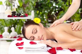 picture of therapist  - Beautiful young woman with flower in head lying on front while massage therapist massaging her back - JPG