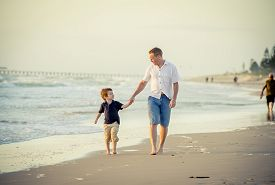 image of barefoot  - young happy father playing on the beach with little son running excited with barefoot in sand and water the kid smiling and having fun together with dad in Summer vacation concept