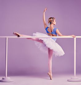 image of ballet barre  - classic ballet dancer in white tutu posing on one leg at ballet barre on a lilac background - JPG