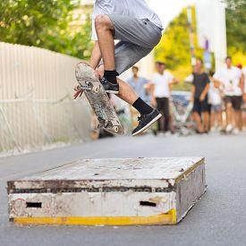 stock photo of skateboard  - Young skateboarder skateboarding on an object in street - JPG