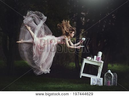 poster of A beautiful blond girl is leaning with a mug of tea over a table. Lack of gravity. Like Alice in Wonderland. A girl with long hair flies like in a fairy tale.
