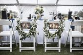 Wedding table under tent, with Mr and Mrs signs on the chairs poster