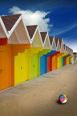 picture of summer beach  - A bright colorful row of summer beach huts on the sand with deep saturated blue sky - JPG