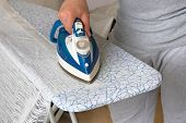 Housework And Household Concept. Man Is Ironing White Textile On Ironing Board. Blue Iron In Man Han poster