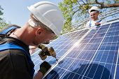 Technician Connecting Solar Photo Voltaic Panel To Metal Platform Using Screwdriver On Bright Blue S poster