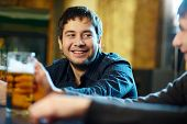 pic of beer mug  - Happy man with glass of beer looking at his friend in pub - JPG