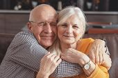 Cheerful Senior Couple Hugging On Sofa At Home poster