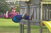 pic of swingset  - A young boy swinging on an outdoor swingset - JPG
