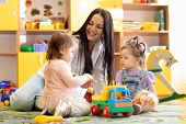Children Kids Toddlers Playing With Teacher In Kindergarten. Nursery Babies Sitting On Floor Togethe poster