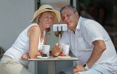 A Middle-aged Couple Makes A Selfie With A Selfie-stick,  While Having Drinks And Desserts At A Stre poster