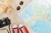 Top View Of Red Gumshoes, Film Camera, Toy Plane, Sunglasses And World Map On Wooden Surface poster
