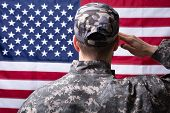 Rear View Of Military Man Saluting Us Flag poster