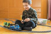 Little Boy Playing With A Toy Railway. Little Boy Playing With Railway Lying On The Floor. Joyful Em poster