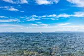 Small Optimist Boat With White Sail, Blue Sky And Sea Background poster