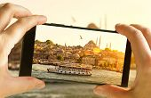 Istanbul At Sunset, Turkey. Taking Photo Of Golden Horn By Cell Phone. Tourist Boat Sails In The Ist poster