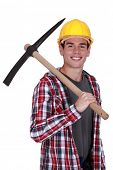Smiling young man with a pickaxe