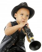 image of biracial  - A biracial preschooler playing a clarinet in a sparkly black fedora and black leather vest - JPG