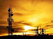 stock photo of telecommunications equipment  - Several radio towers with sunset sky in background - JPG