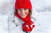 stock photo of snowball-fight  - Happy young woman playing snowball fight on the snow day - JPG