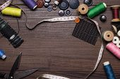 picture of rayon  - threads buttons and needles over brown wooden table - JPG