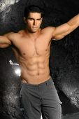 stock photo of hot pants  - Shirtless bodybuilder in gray pants with rocks behind him - JPG