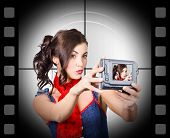 image of selfie  - Young woman recording a movie of herself using video camera - JPG